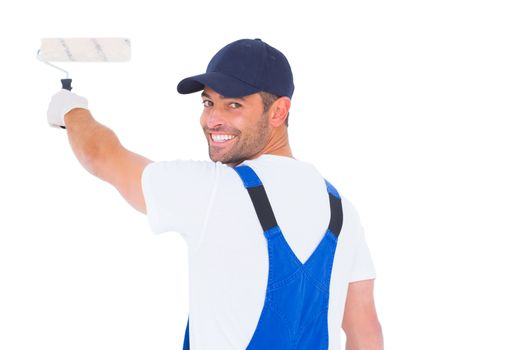 Portrait of handyman in overalls using paint roller