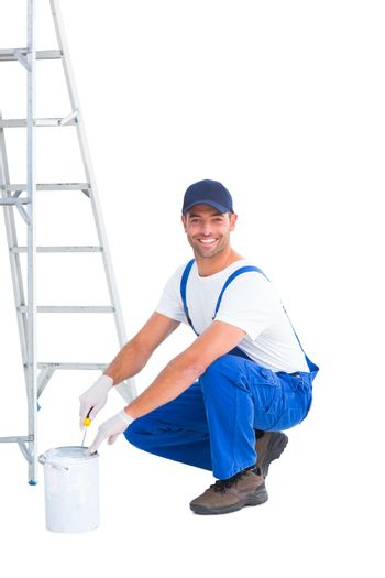 Smiling handyman in overalls opening paint can