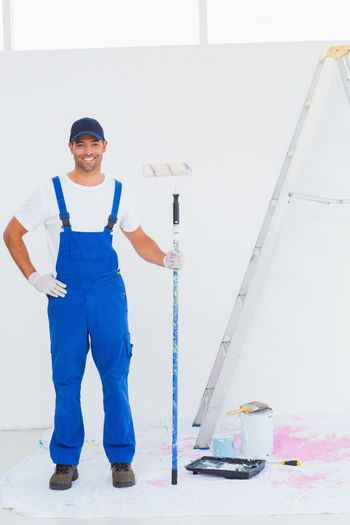 Handyman in overalls holding paint roller at home