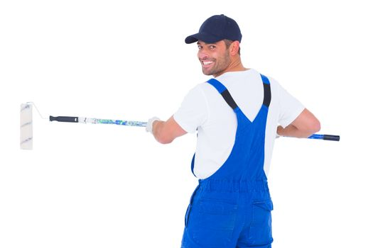 Handyman in overalls using paint roller on white background