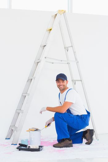 Handyman in overalls opening paint can at home
