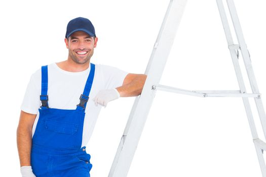 Handyman in overalls leaning on ladder