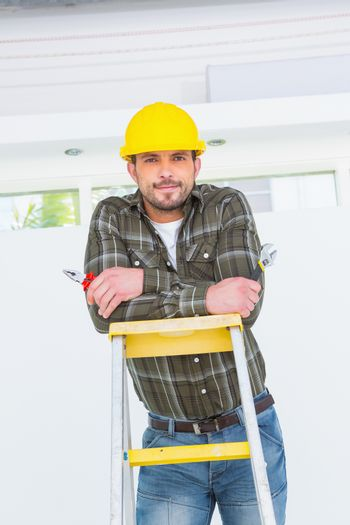 Repairman with pliers on ladder
