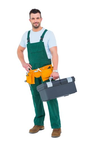 Smiling carpenter with toolbox