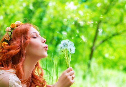 Pretty woman blowing on dandelion