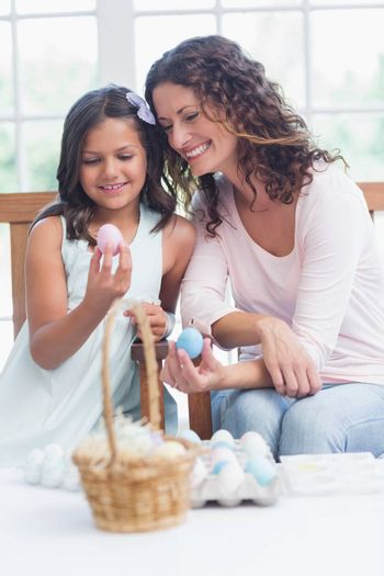 Happy mother and daughter holding easter eggs in the living room