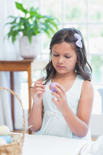 Cute girl painting easter eggs in the living room