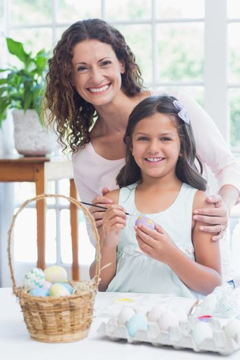 Happy mother and daughter painting easter eggs in the living room