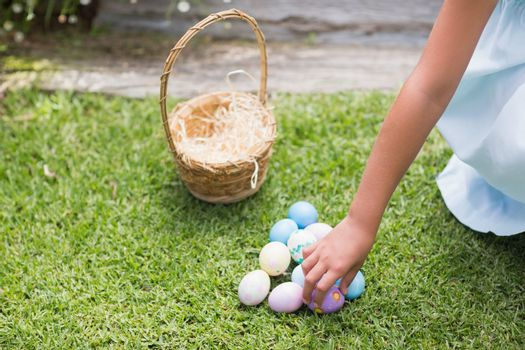 Little girl collecting easter eggs in the garden