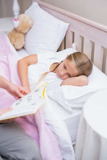 Mother reading daughter a bedtime story