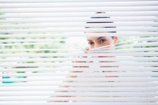 Woman peeking through blinds
