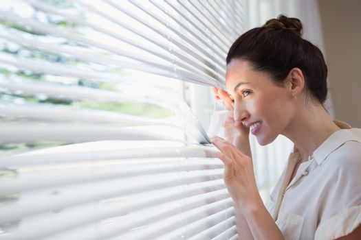 Woman peeking through the blinds