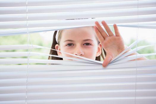 Little girl peeking through blinds