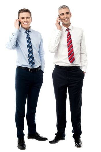 Two male executives talking on cellphone