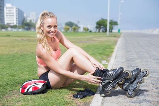 Fit blonde getting ready to roller blade