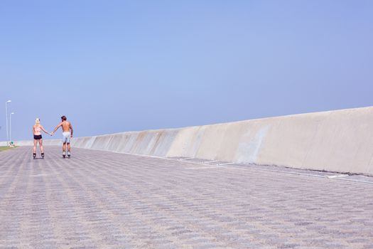 Fit couple rollerblading on the promenade