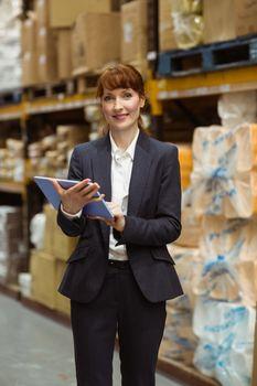 Smiling businesswoman scrolling on digital tablet