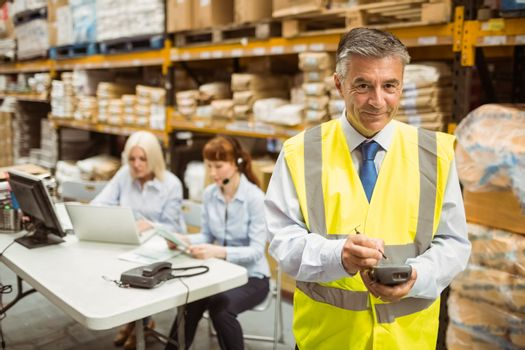 Smiling manager wearing yellow vest using handheld