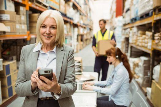 Smiling warehouse manager using handheld