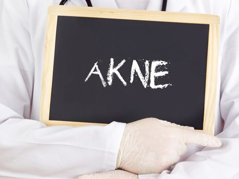 Doctor shows information on blackboard: acne in german