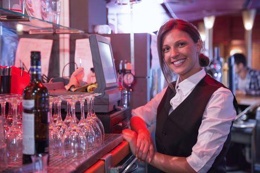 Happy barmaid using touchscreen till