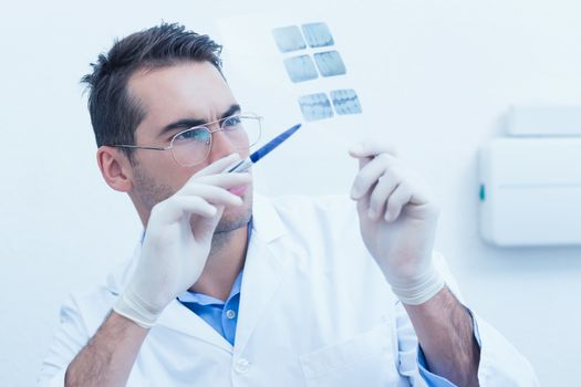 Concentrated male dentist looking at x-ray