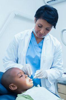 Female dentist examining boys teeth in the dentists chair