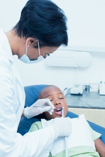 Close up of female dentist examining boys teeth in the dentists chair