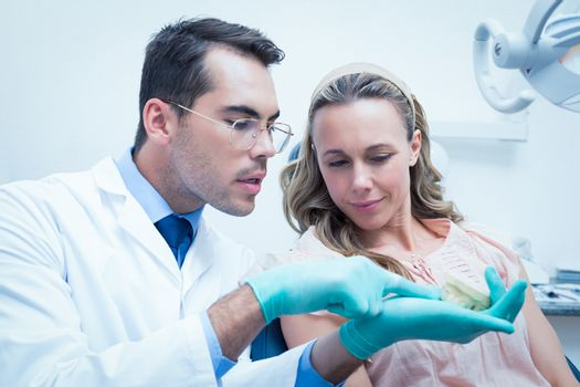 Male dentist showing woman prosthesis teeth