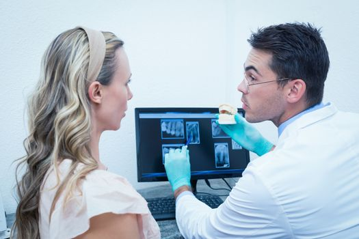 Dentist showing woman prosthesis teeth