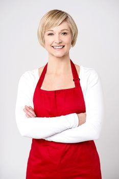 Confident female chef over grey