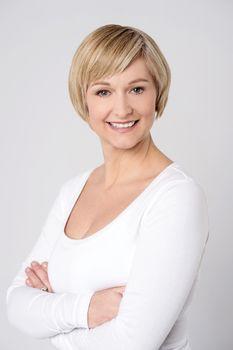 Confident woman posing over grey