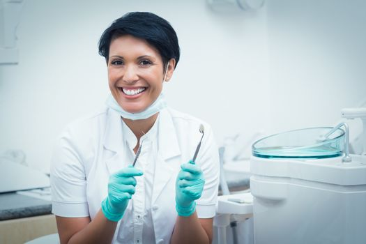 Portrait of happy confident female dentist holding dental tools