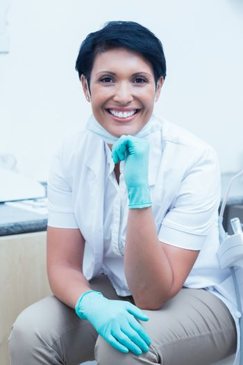 Portrait of confident female dentist with hand on chin