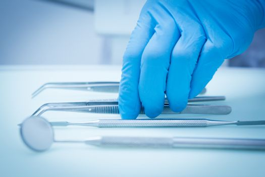 Gloved hand picking dental tools