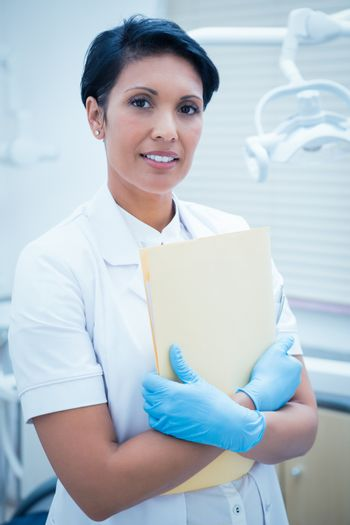 Portrait of female dentist holding reports