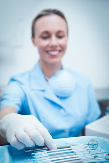 Portrait of female dentist picking dental tools