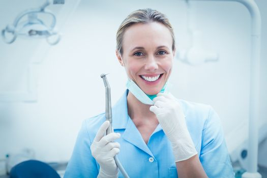 Portrait of smiling young female dentist holding dental tool