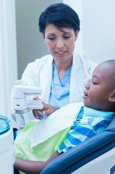 Dentist showing boy prosthesis teeth