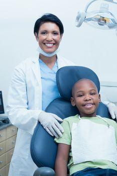Portrait of female dentist examining boys teeth in the dentists chair