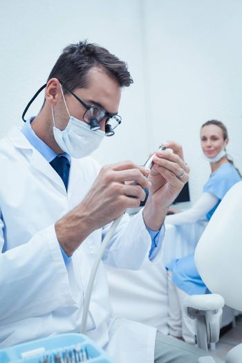 Concentrated young male dentist looking at dental tool