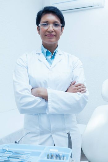 Portrait of confident female dentist standing with arms crossed