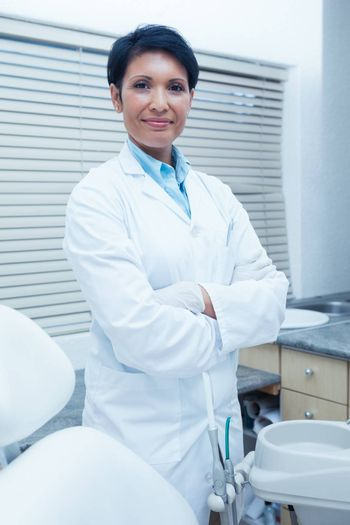 Portrait of smiling female dentist standing with arms crossed