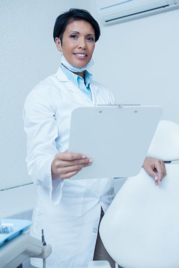 Portrait of smiling young female dentist holding clipboard