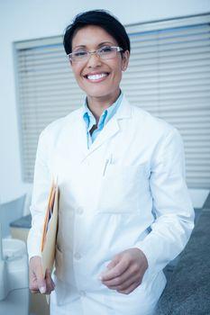 Portrait of smiling young female dentist holding folder