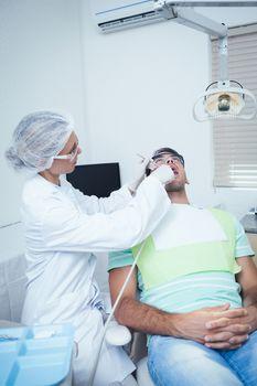 Female dentist examining mans teeth in the dentists chair