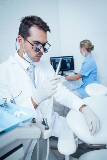 Concentrated male dentist looking at dental drill