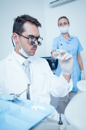 Concentrated male dentist looking at injection