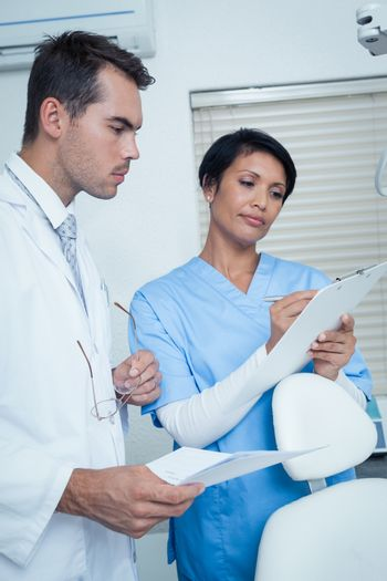 Male and female dentists discussing reports