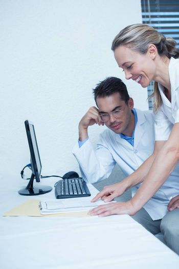 Smiling male and female dentists using computer